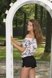 La muchacha adolescente linda presenta cerca del enrejado Foto de archivo libre de regalías