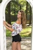 La muchacha adolescente linda presenta cerca del enrejado Foto de archivo