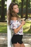 La muchacha adolescente linda presenta cerca del enrejado Fotos de archivo