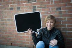 La muchacha adolescente lleva a cabo la muestra negra Fotos de archivo libres de regalías