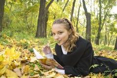 La muchacha adolescente miente en parque del otoño con su diario Imagen de archivo