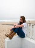 La muchacha adolescente mira en el océano Imagen de archivo libre de regalías
