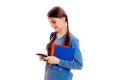 La muchacha adolescente mira en el teléfono y sostener un cuaderno Imagen de archivo