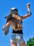 La muchacha adolescente monta su monopatín Fotos de archivo