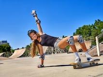 La muchacha adolescente monta su monopatín Fotografía de archivo