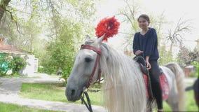La muchacha adolescente monta un caballo en un parque de atracciones metrajes