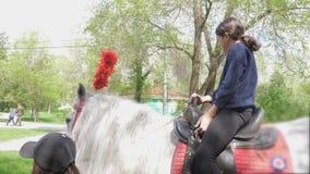 La muchacha adolescente monta un caballo en una forma de vida del parque de atracciones almacen de metraje de vídeo