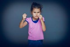 La muchacha adolescente muestra los puños enojados en fondo gris Imagen de archivo