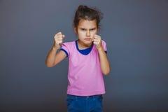 La muchacha adolescente muestra los puños enojados en fondo gris Foto de archivo libre de regalías