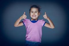 La muchacha adolescente muestra que el gesto da tan en un gris Imagenes de archivo