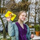 La muchacha adolescente muestra un regalo Imagen de archivo libre de regalías