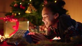 La muchacha adolescente negra está abriendo la caja de regalo de la Navidad debajo del árbol de navidad adornado almacen de video