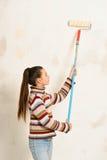 La muchacha adolescente pinta la pared Fotografía de archivo