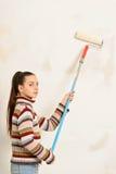 La muchacha adolescente pinta la pared Imagen de archivo