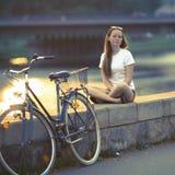 La muchacha adolescente preciosa con la bici se sienta en la costa Imagen de archivo libre de regalías