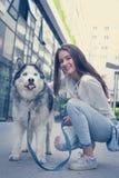 La muchacha adolescente presenta a la cámara con su perro Imagen de archivo libre de regalías