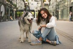 La muchacha adolescente presenta a la cámara con su perro esquimal Foto de archivo libre de regalías