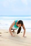 La muchacha adolescente que ejercita en la playa cerca del océano azul riega Imagen de archivo libre de regalías
