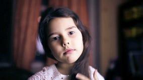 La muchacha adolescente que el niño endereza el pelo se peina el pelo almacen de metraje de vídeo