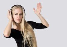 La muchacha adolescente que escuchaba la música en los auriculares aisló el fondo blanco Fotografía de archivo