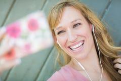 La muchacha adolescente que lleva los auriculares toma Selfie con el teléfono elegante Imagen de archivo