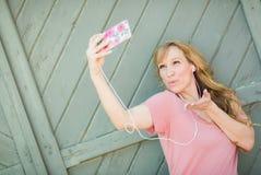 La muchacha adolescente que lleva los auriculares toma un Selfie con el teléfono elegante Foto de archivo