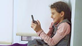 La muchacha adolescente que se sienta en el web un travesaño de la ventana juega al juego online para el smartphone Imagen de archivo