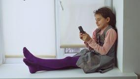 La muchacha adolescente que se sienta en un travesaño de la ventana juega al juego online para el smartphone del web Foto de archivo libre de regalías