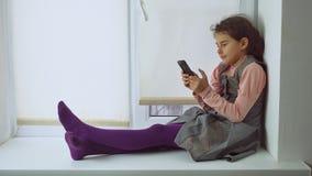 La muchacha adolescente que se sienta en un travesaño de la ventana juega al juego online para el web del smartphone Foto de archivo