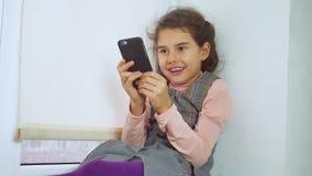 La muchacha adolescente que se sienta en un travesaño del web de la ventana juega al juego online para el smartphone Imagen de archivo libre de regalías