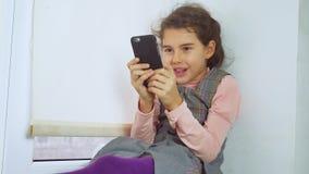La muchacha adolescente que se sienta en un web del travesaño de la ventana juega al juego online para el smartphone Foto de archivo libre de regalías