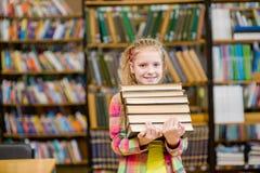 La muchacha adolescente que sostiene la pila reserva en la biblioteca Fotos de archivo libres de regalías