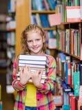 La muchacha adolescente que sostiene la pila reserva en la biblioteca Foto de archivo