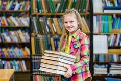 La muchacha adolescente que sostiene la pila reserva en la biblioteca Imágenes de archivo libres de regalías