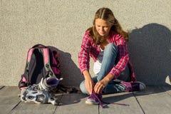 La muchacha adolescente quita las zapatillas de deporte y viste los pcteres de ruedas al aire libre Imagen de archivo