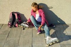 La muchacha adolescente quita las zapatillas de deporte y viste los pcteres de ruedas al aire libre Se sienta en fondo de la pare fotografía de archivo
