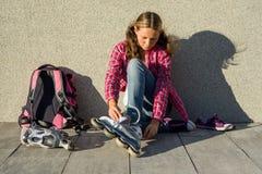 La muchacha adolescente quita las zapatillas de deporte y viste los pcteres de ruedas al aire libre Si Foto de archivo libre de regalías