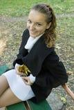 La muchacha adolescente ríe en el banco en parque del otoño Imágenes de archivo libres de regalías