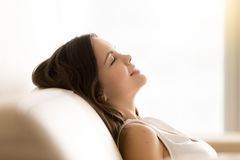 La muchacha adolescente relajada sueña con los ojos cerrados en el sofá Imagen de archivo