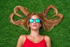 La muchacha adolescente rubia con el corazón del pelo forma la mentira Imagen de archivo libre de regalías