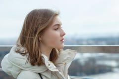 La muchacha adolescente rubia del estudiante adorable joven mira en la distancia en la plataforma de observación con vistas al ci Imágenes de archivo libres de regalías