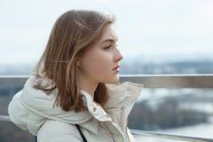 La muchacha adolescente rubia del estudiante adorable joven mira en la distancia en la plataforma de observación con vistas al ci Foto de archivo