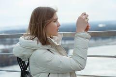 La muchacha adolescente rubia del estudiante adorable joven toma las fotos con smartphone en la plataforma de observación con vis Imágenes de archivo libres de regalías