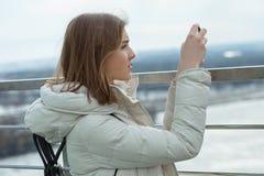 La muchacha adolescente rubia del estudiante adorable joven toma las fotos con smartphone en la plataforma de observación con vis Imagen de archivo