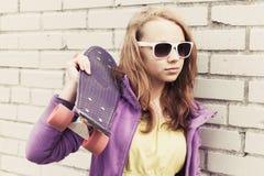La muchacha adolescente rubia en gafas de sol sostiene el monopatín Foto de archivo