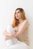 La muchacha adolescente rubia hermosa que mira para arriba se está sentando con una de ella Imágenes de archivo libres de regalías