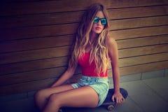 La muchacha adolescente rubia se sienta en patín en una pared de madera Foto de archivo libre de regalías