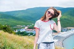 La muchacha adolescente 17s se coloca en la colina en los vidrios de sol que miran la cámara Imagen de archivo