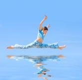 La muchacha adolescente salta en fondo azul Foto de archivo