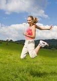 La muchacha adolescente salta en prado Fotos de archivo libres de regalías